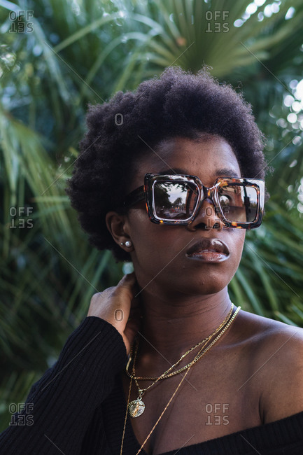 Serious African American female with Afro hairstyle in trendy glasses against palms