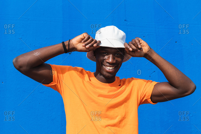 Young cheerful African American male in bright yellow t shirt adjusting white cap while standing against blue wall