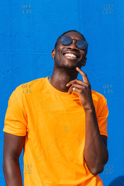 Young cheerful African American male in bright yellow t shirt and sunglasses looking upwards standing against blue wall