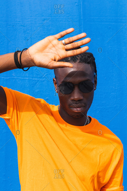 Serious young African American guy in bright yellow t shirt and trendy sunglasses looking at camera against blue background