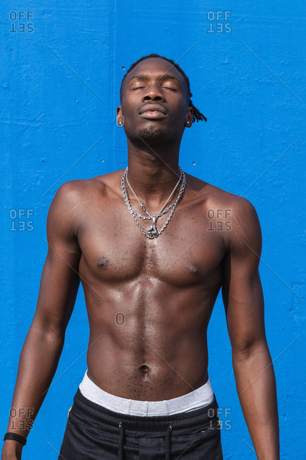 Confident shirtless young African American male with strong muscular body with metal chains on neck standing wit eyes closed against blue background