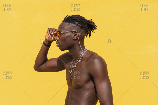 Serious young shirtless African American male in stylish sunglasses and with metal necklaces posing against yellow wall with striped shadow