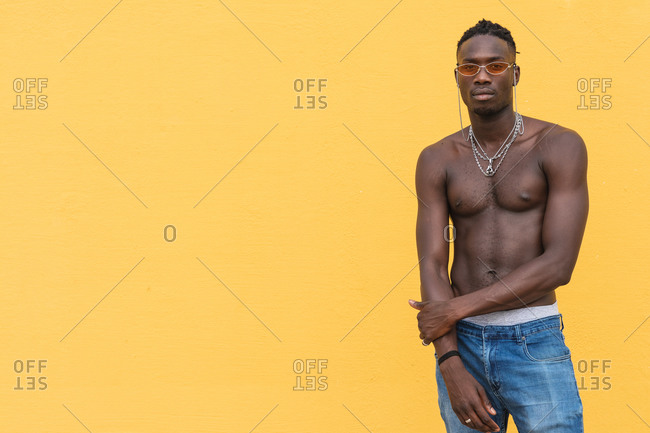 Serious young shirtless African American male with metal necklaces posing against yellow wall