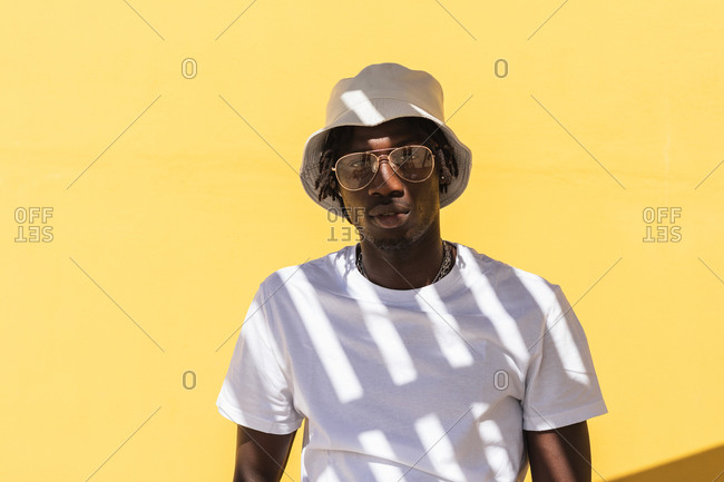 Modern hipster African American guy with striped shadow on white t shirt wearing sunglasses and panama hat and looking at camera while standing against yellow wall
