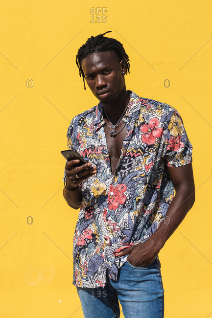 Confident young hipster African American male with dreadlocks wearing trendy summer shirt with floral print and jeans using mobile phone and looking at camera against yellow background