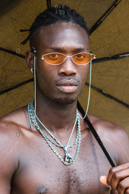 Serious young African American guy with naked torso and dreadlocks wearing trendy sunglasses and metal chains holding open umbrella and looking at camera