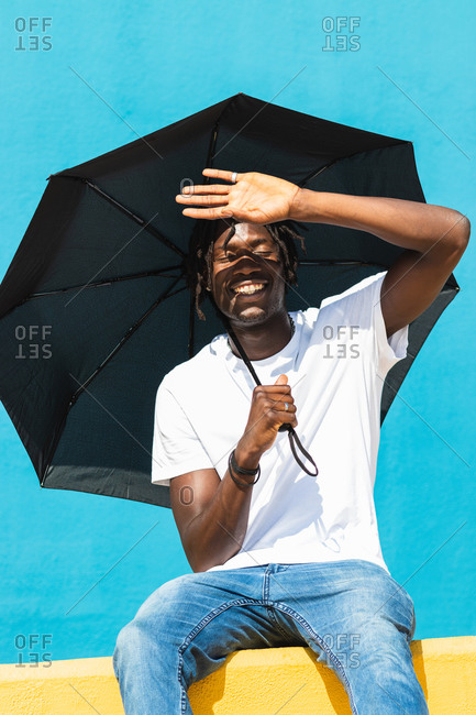 Low angle of cheerful African American guy in casual outfit with black umbrella covering eyes from bright sunlight while sitting on yellow fence against blue background