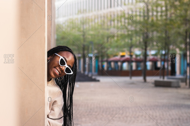 Happy young black female in stylish sunglasses peeking from behind pillar and smiling on city street