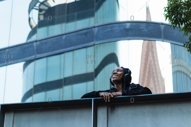Low angle of delighted black woman looking up and smiling while leaning on bridge barrier and listening to music on city street