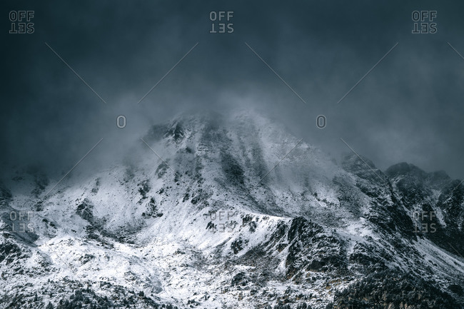 Majestic panoramic scenery of rough rocky slopes of mountain range covered with snow under cloudy sky