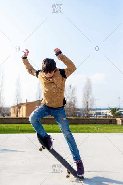 Teenage skater jumping with skateboard and showing trick during ride in skate park