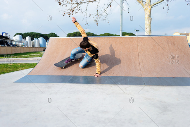 Teenage boy performing trick on skateboard on ramp while practicing tricks on sunny day