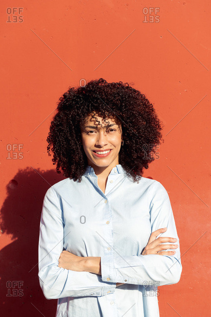 Cheerful ethnic female entrepreneur wearing formal shirt standing with crossed arms on street and looking at camera