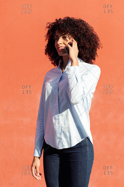 Content ethnic female entrepreneur in formal shirt speaking on smartphone while standing in city on orange background