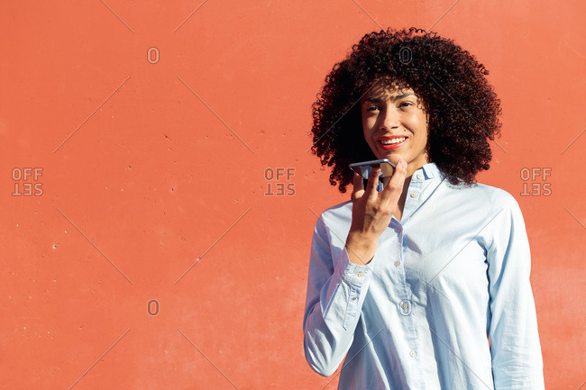 Content ethnic female entrepreneur in formal shirt recording voice message on smartphone while standing in city on orange background