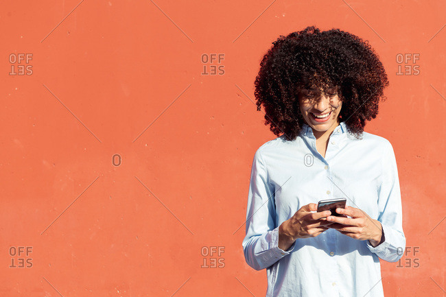 Content ethnic female entrepreneur in formal shirt texting on smartphone while standing in city on orange background