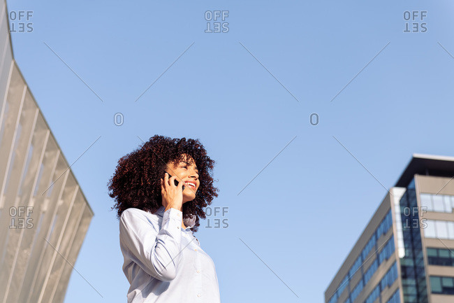 From below of cheerful ethnic female entrepreneur standing in downtown and having conversation on mobile phone while looking away