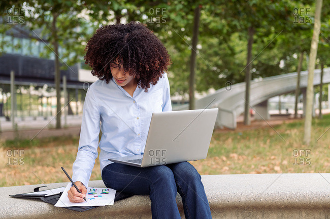 Focused female entrepreneur sitting on stone bench in park and working remotely while on laptop and taking notes in documents