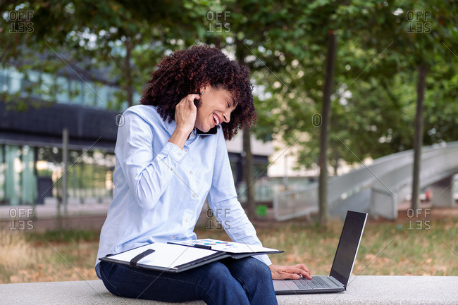 Smiling female entrepreneur sitting on stone bench in park and working remotely while speaking on smartphone and taking notes in documents