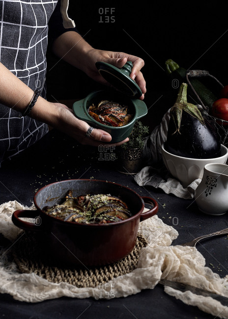 Crop anonymous housewife cooking traditional ratatouille dish with fresh vegetables in home kitchen