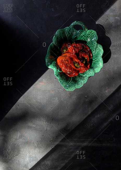 Top view of green ceramic bowl with baked red bell peppers placed on gray table