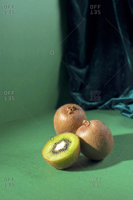 From above composition of fresh natural green kiwis arranged on green background