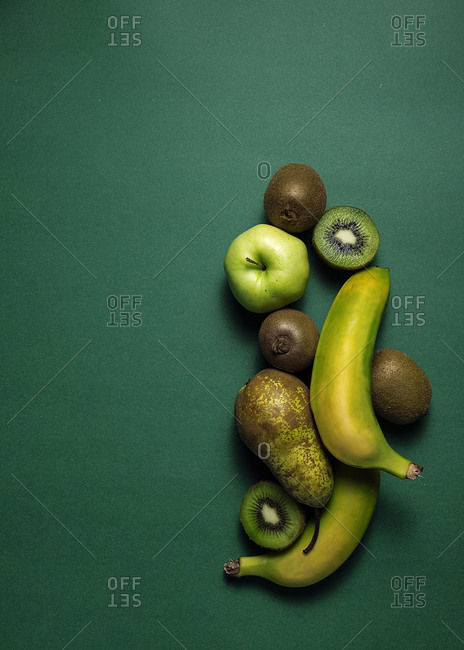 From above composition of fresh natural green pear and apple with kiwi and banana arranged on green background