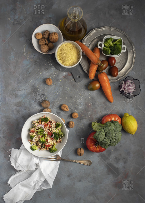 Top view of bowl with healthy homemade bulgur couscous salad with various vegetables and walnuts served on table with ingredients