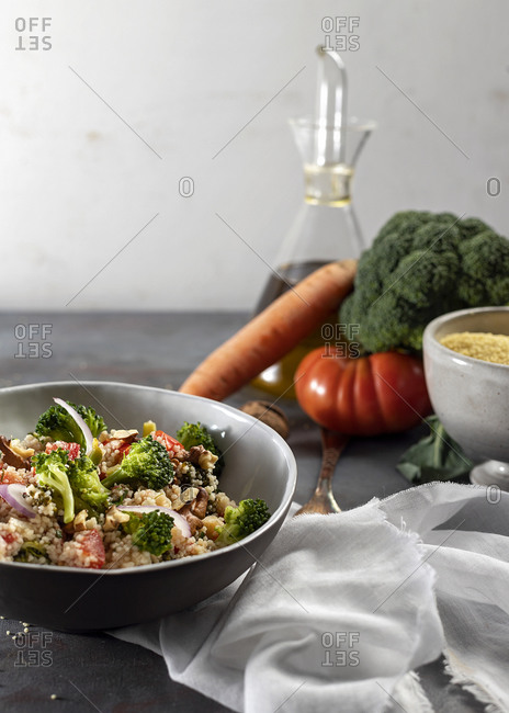 Bowl with healthy homemade bulgur couscous salad with various vegetables and walnuts served on table with ingredients