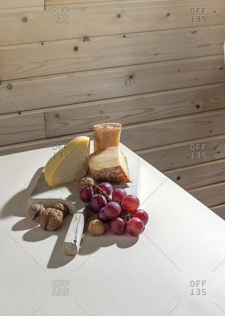 Rustic composition with aromatic artisan cheese served with ripe red grapes and walnuts on white table near wooden wall