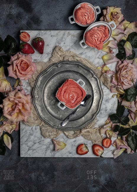 Top view composition with delicious homemade strawberry sorbet served on table with fresh berries and rose flowers