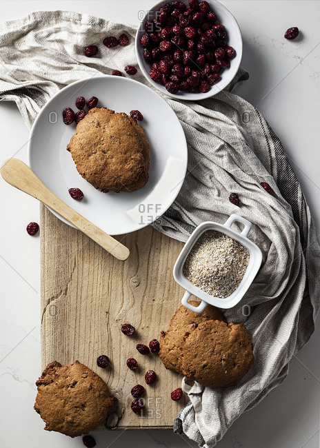 From above of delicious homemade cookies with dried cranberries arranged on wooden cutting board on table in kitchen