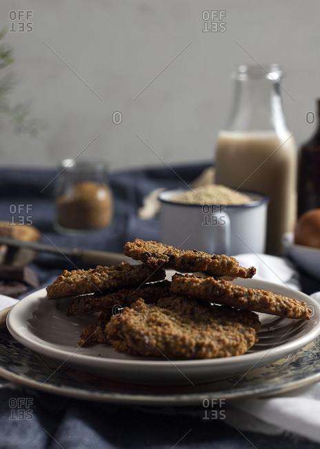 High angle of appetizing homemade oatmeal cookies placed on table with assorted ingredients