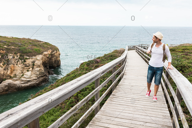 Full body of active travelling man in casual outfit and hat with backpack exploring nature while walking along wooden walkway in countryside
