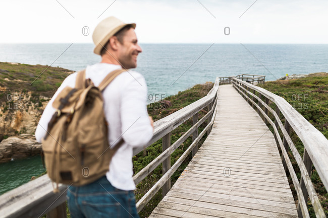 Back view of active travelling man in casual outfit and hat with backpack exploring nature while walking along wooden walkway in countryside