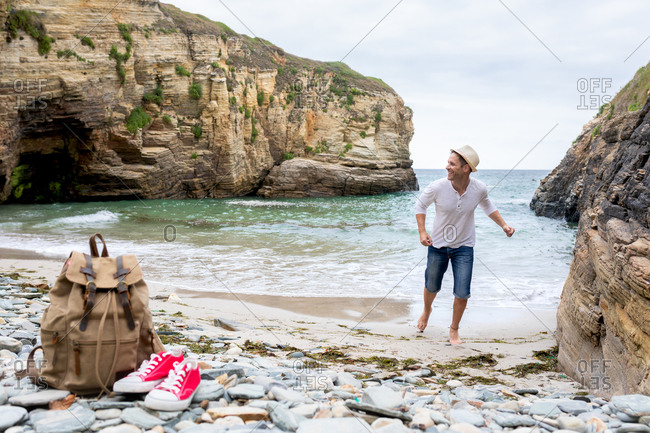 Delighted male tourist running at wet seashore with backpack and gumshoes and enjoying vacation in summer