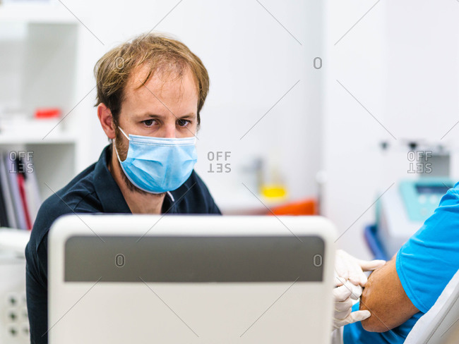 Man in medical mask focusing on computer monitor while examining arm of crop patient with ultrasound probe in hospital