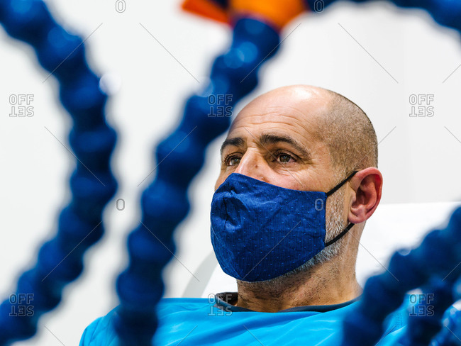 Bald mature man in fabric mask looking away behind physiotherapy equipment during pandemic in hospital