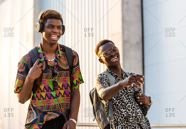 Delighted African American male friends in stylish outfit enjoying stroll in city and laughing at joke together