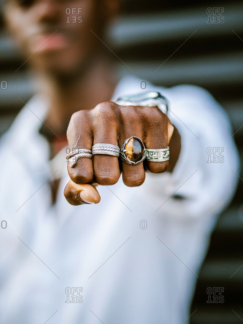 Blurred anonymous African American stylish male showing fist with various trendy silver rings