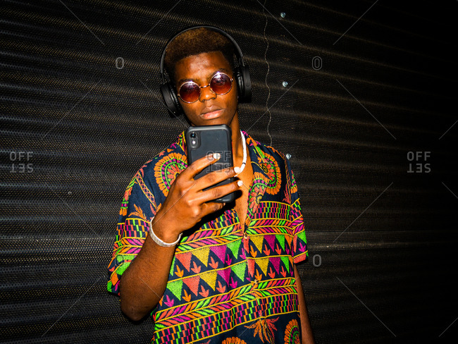 Young black male in vibrant trendy shirt standing on street at night and browsing smartphone while listening to music in headphones