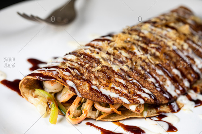 Closeup of delectable crepe filled with tonkatsu and seafood and placed on plate in Japanese restaurant