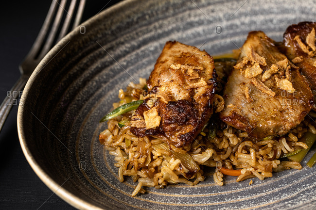 Closeup of palatable spiced pork meat and rice chaufa in plated on table in expensive restaurant