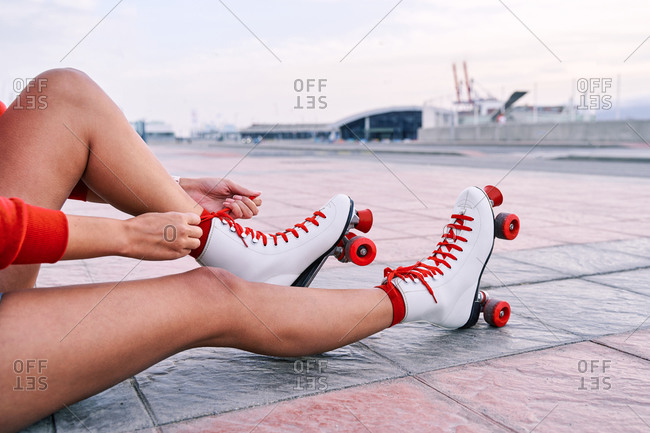From above of legs of crop female tying shoelaces on retro roller skates sitting on the floor in city
