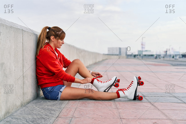 Side view of female sitting on street and tying shoelaces on roller skates while entertaining in city