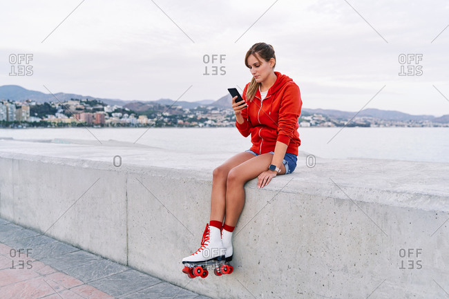 Female wearing retro roller skates sitting on embankment using smartphone during weekend in city