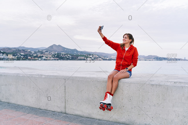 Smiling female wearing retro roller skates sitting on embankment and taking photo on selfie camera during weekend in city