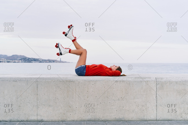 Side view of young carefree female wearing roller skates lying with raised legs on stone border on promenade and enjoying weekend in city