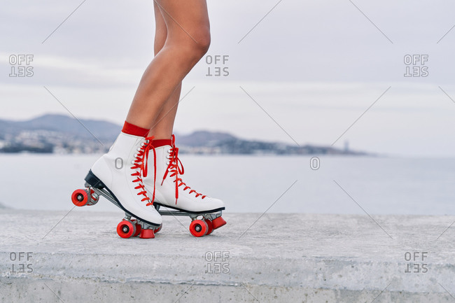 Crop faceless female with slim legs and in red and white roller skates standing on stone border on background of sea