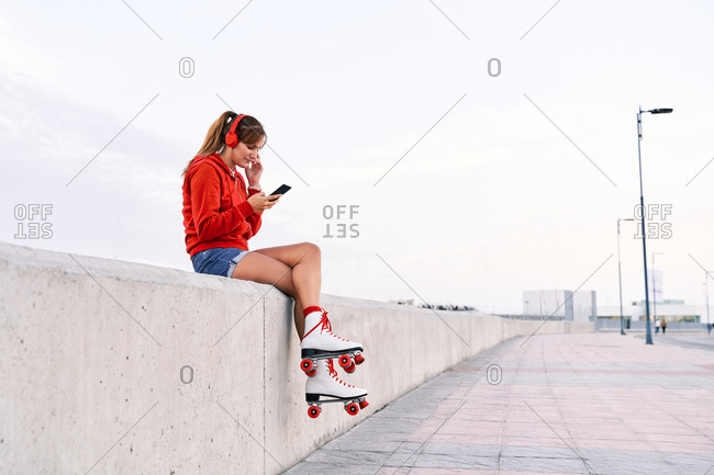 Side view of relaxed female in roller skates sitting on embankment and listening to music in headphones while enjoying weekend